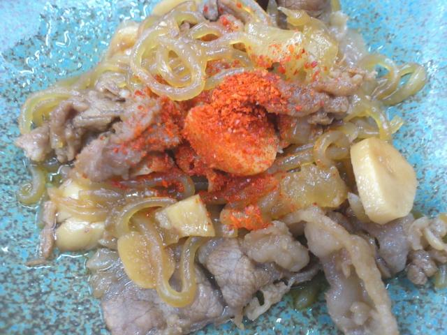 糸コン入りの牛肉煮で味の染み込んだニンニクスライスがちりばめられた一品。 素晴らしいビジュアル。 逆となりのオッサン真似して一味投入で、 たまらんビジュアルに。